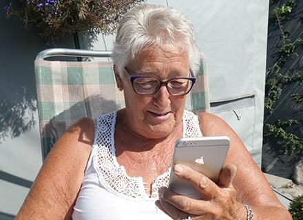 seniorin mit iphone guckt auf bildschirm